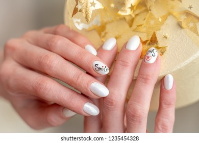gift Packed in Golden paper bandaged by a ribbon decorated with a bow made of fabric. beautiful box in hand. manicure on hands brought pearl tone glossy finish nails. the holiday atmosphere fills