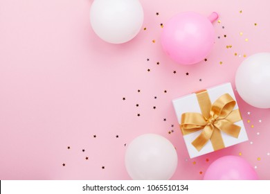 Gift or present box, balloons and confetti on pink table top view. Flat lay composition for birthday, mother day or wedding.