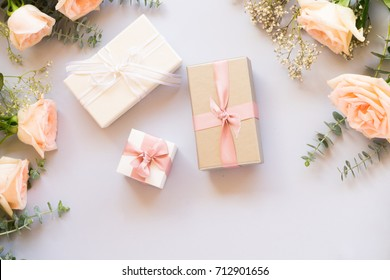 gift or present box and flowers on blue table from above