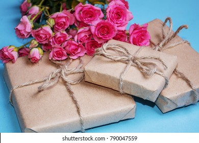 gift or present box and flowers on blue table . paper blank and pink rose flower