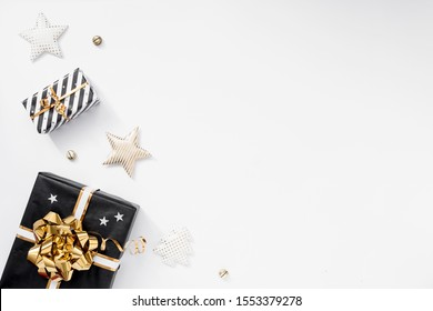 Gift or present box, party hats and stars on white table. Christmas composition with black and golden decorations