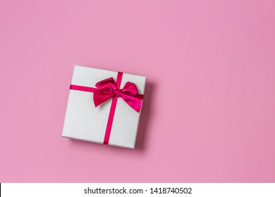 Gift present box with satin bow on light pink background, top view