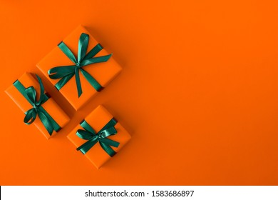 Gift present boxes on orange background. Flat lay. Top view with space for text