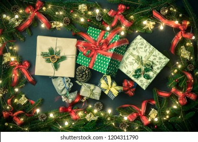 Gift present boxes in vertical top view dark blackboard with pine branches,ribbons, lights decorated frame.Xmas winter holiday season party social media card background