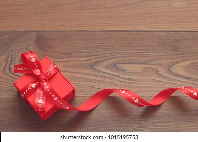 Gift red box with a ribbon on a wooden table