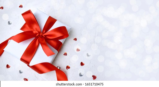 Gift and red hearts  on white background. Greeting concept for Valentines day, Mothers day, Women day or wedding. Bokeh lights. Banner with copyspace.