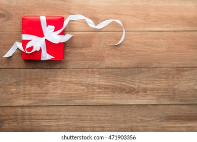 gift in red packing on a wooden background