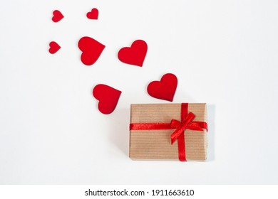 a gift with a red ribbon with hearts on a light background. Top view