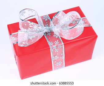 Gift in red wrapping with silver bow on white background