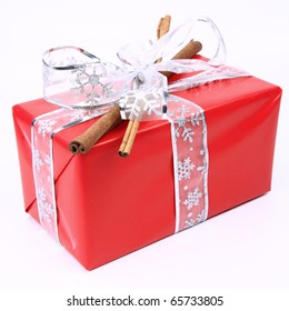 Gift in red wrapping with a silver bow decorated with cinnamon sticks on white background