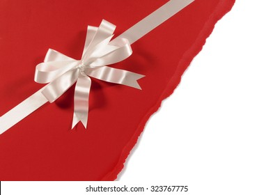 Gift ribbon bow in white satin on untidy torn red paper background
