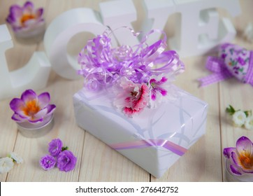 A Gift with ribbons and flowers. White letters forming word LOVE on wooden background, soft focus