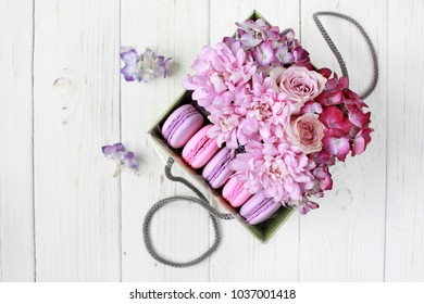 Gift set: box with flowers (hydrangea, rose, chrysanthemum) and macaroni on a wooden background. Selective focus, top view.
