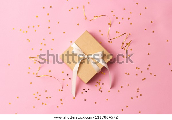 gift and sparkles of confetti on a colored background top view. minimalism, insta. flatlay