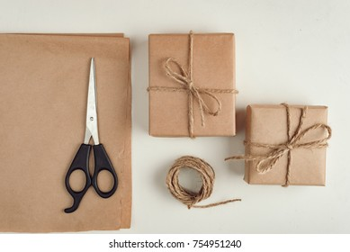 gift, a surprise in the box is packed in brown vintage paper and tied with a rope, scoop. Christmas concept. on a white homogeneous background.near the scissors