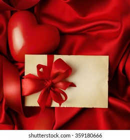 Gift tag on red silk background. valentines day. copy space for text