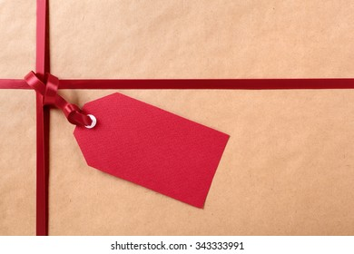Gift tag with red ribbon, brown parcel wrapping paper background, copy space.