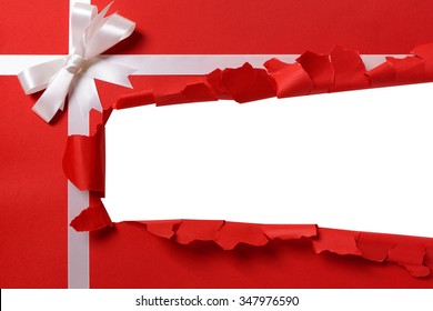 Gift torn open strip, white ribbon bow, red paper background