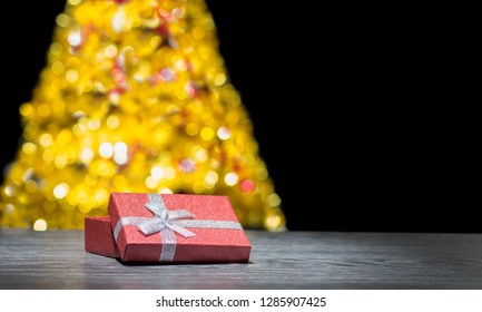 Gift under the Christmas tree. Christmas gift. Christmas background. Gift box on the background of a Christmas tree. A place for an inscription, wishes.