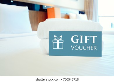 Gift voucher concept. Gift voucher card placed inside a hotel room bed with White towel.