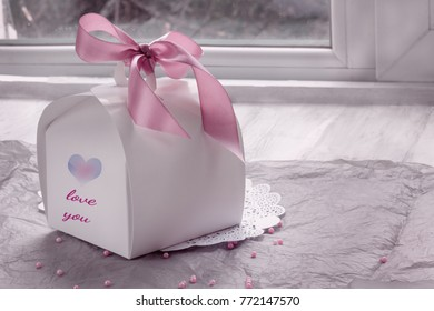 Gift white box with an inscription I love you and my heart on a wooden background with beads