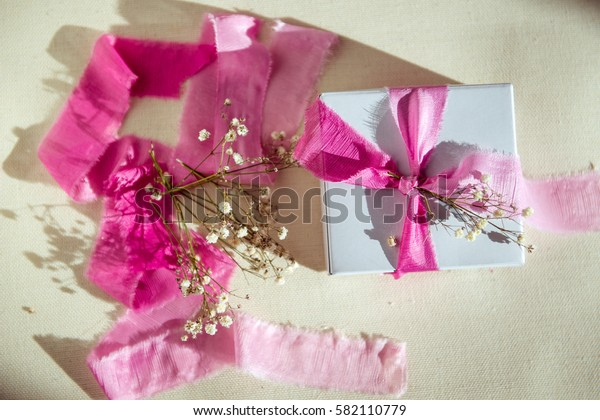 gift in a white box and pink ribbon