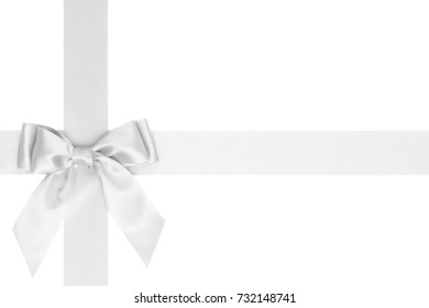 Gift white silk bow with tails on wide cross ribbon isolated on white