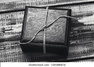 Gift wooden box. Wooden box with a gift on a wooden background close-up. Black and white photo