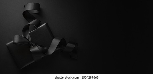 Gift wrapped in black paper with black bow on dark background. View from above. Banner
