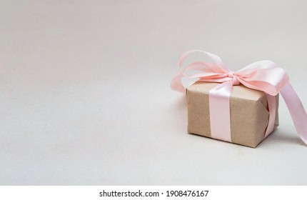 The gift, wrapped in craft and tied with a pink ribbon, is located on the craft background on the right. There is a space for text on the left. Banner. Postcard for the holiday.