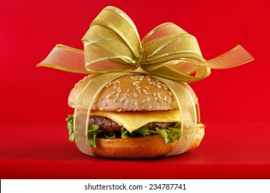 Gift wrapped hamburger , conceptual food image with red background