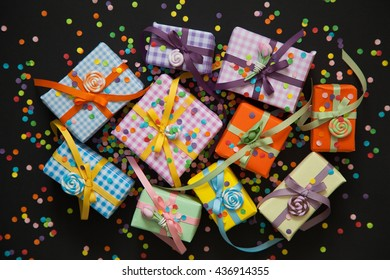 Gift wrapped in paper. Small gifts are packed in colored paper. Colored ribbons. Gift wrapping. Black background. View from above. Pastel shades.