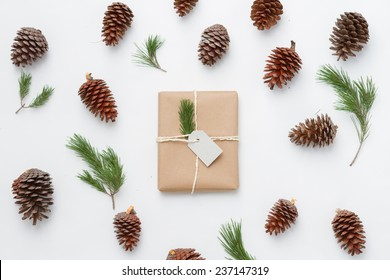 Gift wrapped with pinecone and pine branch over white background