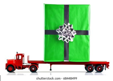 A gift wrapped present being delivered on a flatbed lorry. Isolated on a white background. Truck is a model.