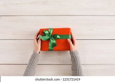 Gift wrapping background. Female hands holding handmade present box in red paper against white wooden table background. Bithday or christmas preparation concept, top view, copy space
