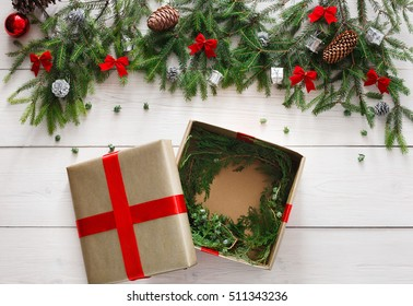 Gift wrapping background. Open box for Christmas present in paper decorated with satin ribbon. Winter holidays concept. Top view of white wood table with fir tree branches, ornaments and garlands