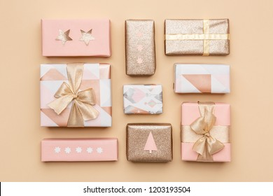 Gift wrapping composition. Beautiful nordic christmas gifts isolated on gold background. Pink and gold colored wrapped xmas boxes.