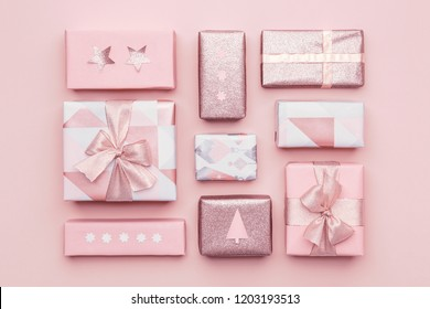 Gift wrapping composition. Beautiful nordic christmas gifts isolated on pastel pink background. Pink colored wrapped xmas boxes.