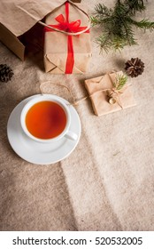 Gift wrapping and letters, cards for Christmas greetings. Envelopes with letters, gifts, Christmas tree branches and pine cones are on a wooden table lie, a cup of fragrant hot tea, top view