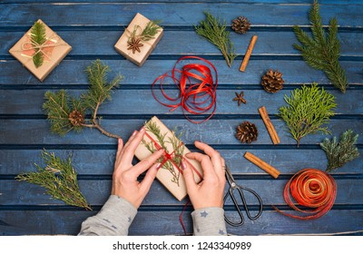 Gift wrapping. Packaging christmas present boxes. Top view of hands with fir tree, cedar, juniper, branches. Preparation for holidays. Hand crafted gifts.