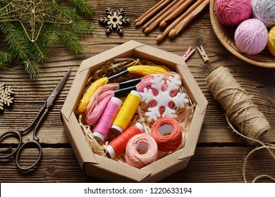 Gift wrapping. Present for the needlewoman - thread, floss, needles, hook, cotton yarn. Composition with box, festive decoration and fir tree branch. Merry Christmas and Happy New Year concept