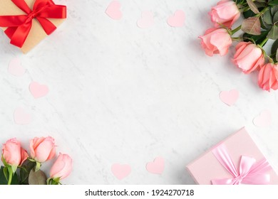 Giftbox and pink rose flower on marble white table background for Mother's Day holiday greeting design concept.