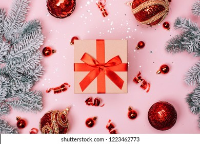 Giftbox with red big and small christmas baubles and snow fir-tree on pink pastel background. Flat lay. New year concept.