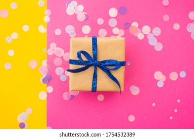 Giftbox tied with blue color ribbon on bright pink, pastel yellow background with colorful confetti and glitter. Festive background.