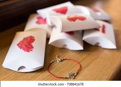 Gifted box ideas for weddings. Party favor boxes with red hearts. Charm bracelet and box for Valentine's Day. Mini boxes for gifts. Group of white boxes with red hearts and a charm bracelet.