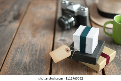 Gifts with blank label on a wooden background
