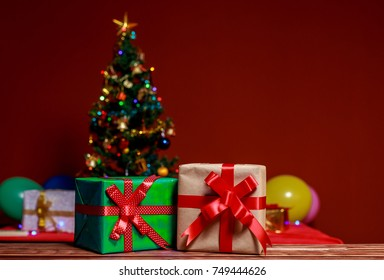 Gifts box with red bow on wooden table at Christmas tree lights blurred on red background.Christmas concept,selective focus