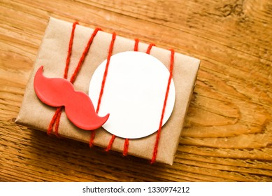 gifts box wrapped in brown craft paper and with red ribbon isolated on wooden background. empty round sticker - happy father's day. red paper mustache sticker on present box