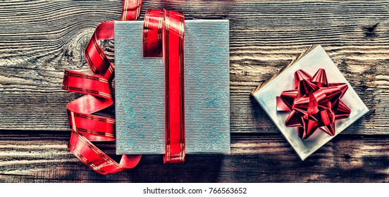 Gifts in boxes with red bows. Christmas gifts on a wooden background, Top view.