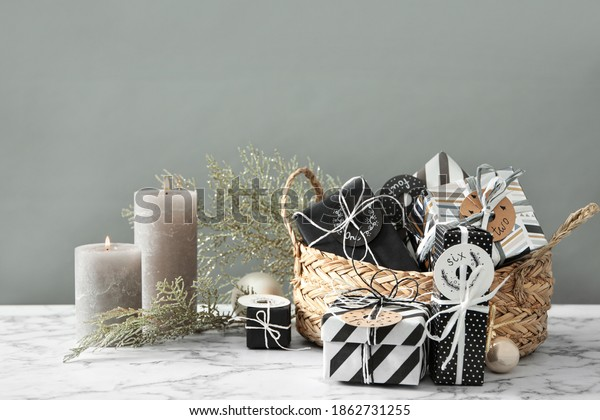 Gifts for Christmas advent calendar, burning candles and festive decor on white marble table against grey background